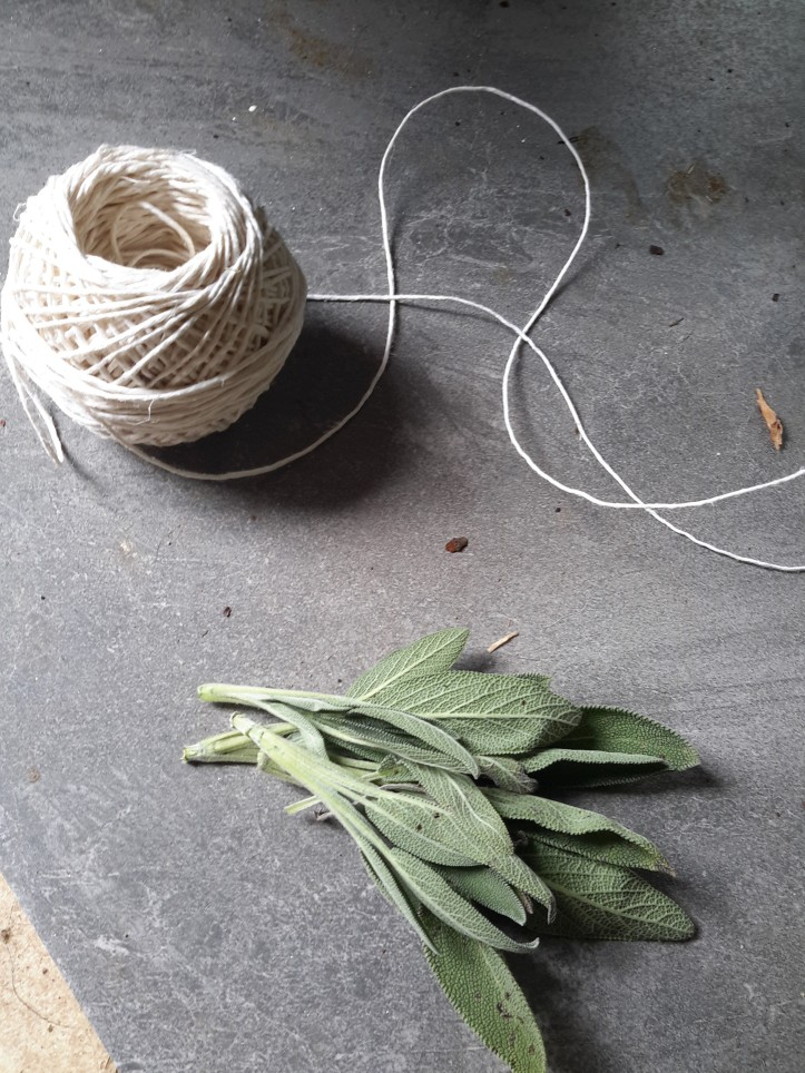 A bundle of sage and a ball of white cotton twine placed on a dark grey ceramic tile.