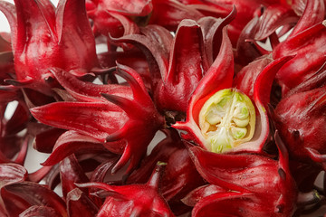 Full image containing roselles one is cut in half showing green seed pod shem fruit I'd ripe.