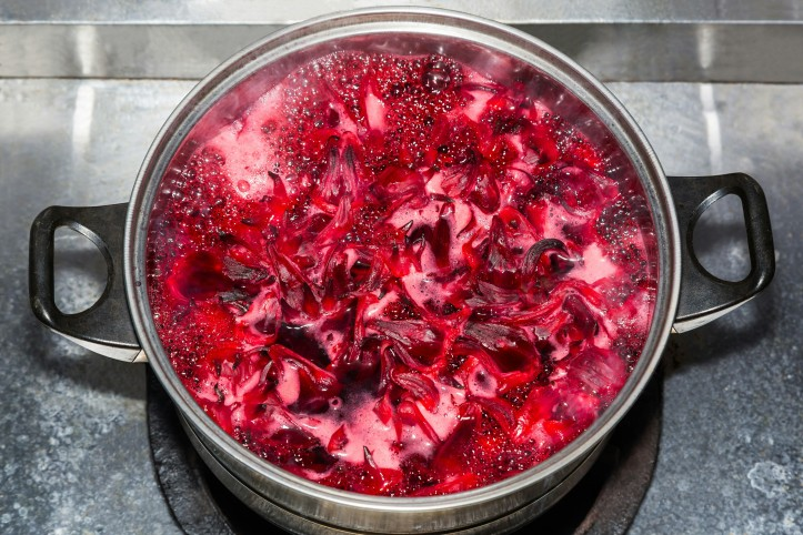 Brightly coloured Rosselle jam boiling away in pot.