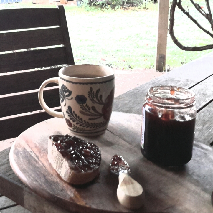 Cup if tea and sourdough rye toast slathered in Roselle jam on a wooden board with jam jar and knife, on a wooden outdoor table setting.green lawn in the background.