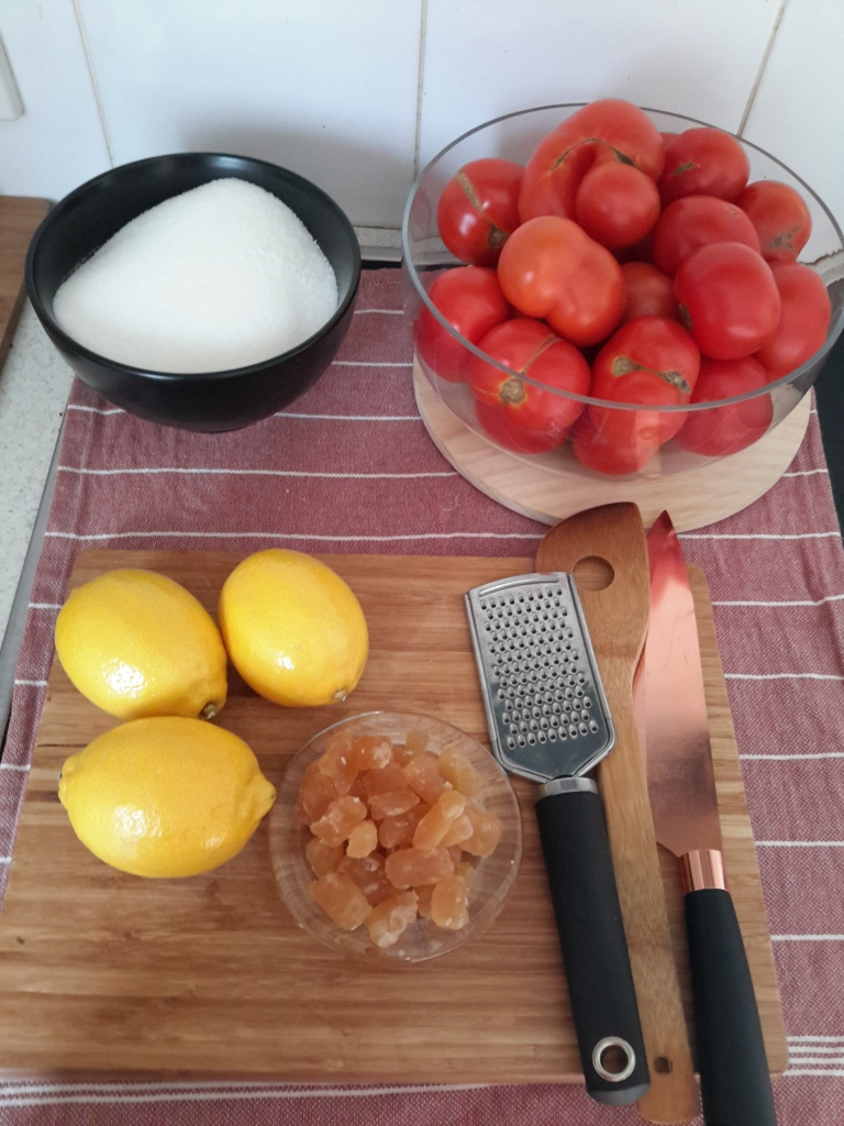 Bowl of fresh tomatoes, bowl of sugar, three lemons small bowl of Glace ginger on wooden Baird with greater and copper knife.