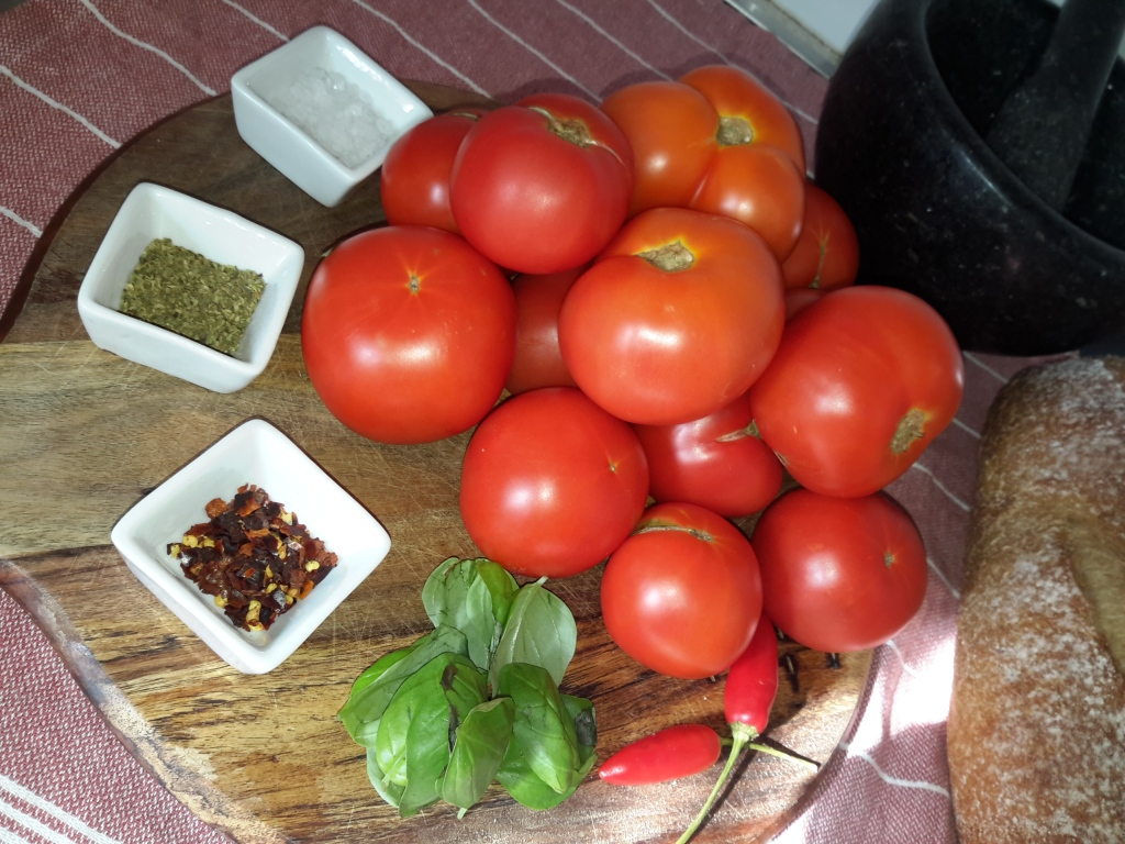 Ripe tomatoes on a wooden board,along side are small square vessels filled with spice and fresh basil sprig.