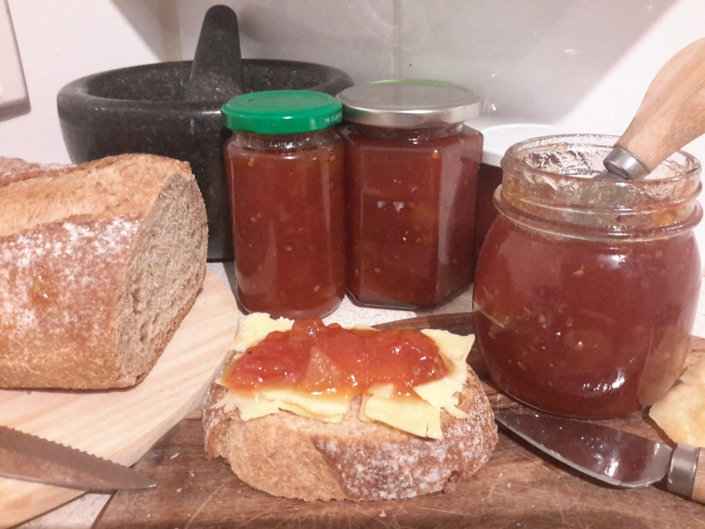 On a wooden board a slice of sour dough with slices of brie chesse, covered in tomato jam,  in the background jars of tomato jam.