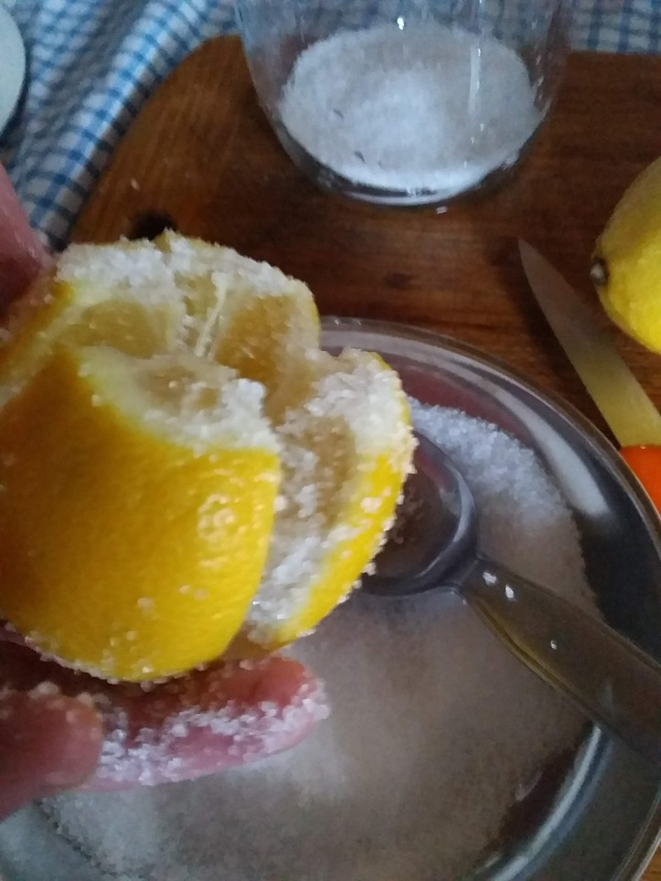 Converting quartered lemon inside and out with sea salt.